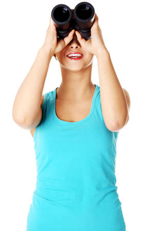 Teen caucasian student smiling and looking through binoculars. Isoalted on white background photo