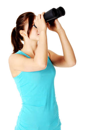 Teen student looking up through black binoculars. Isolated on white background. photo