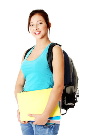 Pretty smiling caucasian student with backpack standing and holding notes.   photo