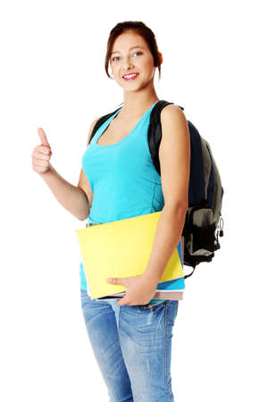 Pretty caucasian girl with backpack holding notes and showing her thumb-up. Isolated on white. photo