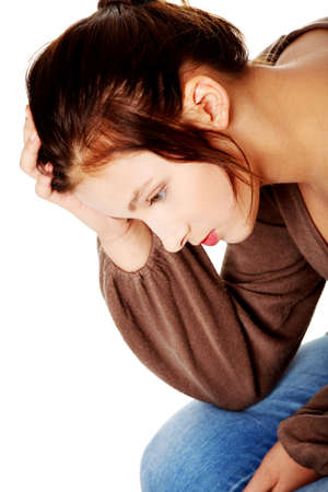 Sad caucasian pretty teen student thinking and touching her head. Stock Photo - 11254198