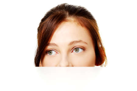 Pretty teen brunette student hiding behind sheet of paper. Stock Photo - 11254005