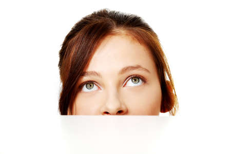 Pretty teen brunette student hiding behind sheet of paper. Stock Photo - 11254050