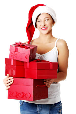 Pretty smiling teen caucasian girl in Santa`s hat holding gifts. Isolated on white. photo