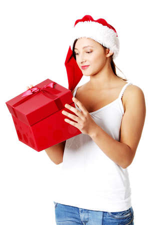Pretty caucasian teen girl opening a gift. Isolated on white. photo