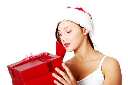 Pretty caucasian teen girl holding and looking at gift. Isolated on white. photo