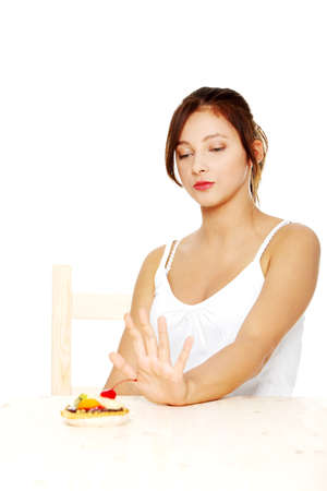 Pretty teen girl on diet showing stop gesture to cake. Isoalted on white. Stock Photo - 11253920