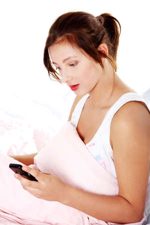 Teen pretty caucasian girl reading message on her mobile over white background. photo