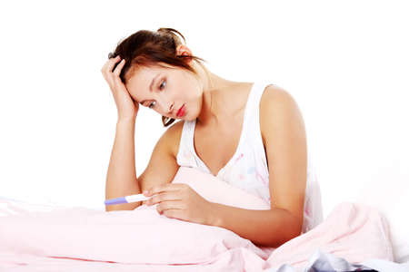 conceive: Teen pretty depressed girl checking her pregnant test in bed.
