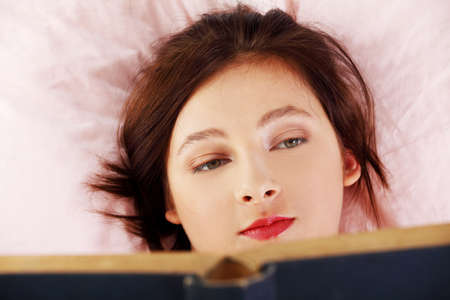 Pretty caucasian girl lying in bed and reading a book. Stock Photo - 11254212