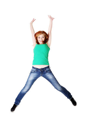 Teen caucasian student jumping and raising hands in the air. Isolated on white. photo