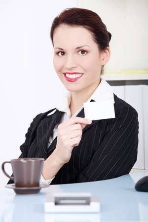 Pretty caucasian smiling businesswoman showing white card. photo