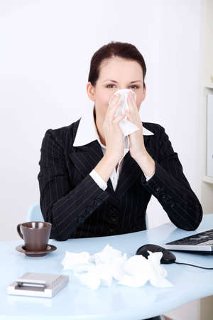 Pretty caucasian businesswoman blowing her nose in the office. photo