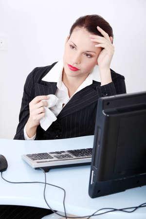 Pretty caucasian sick businesswoman holding a tissue in the office. photo