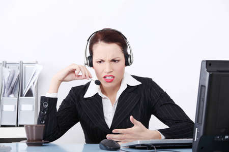 Front view of an beautiful business woman shouting through the headphones at work. photo
