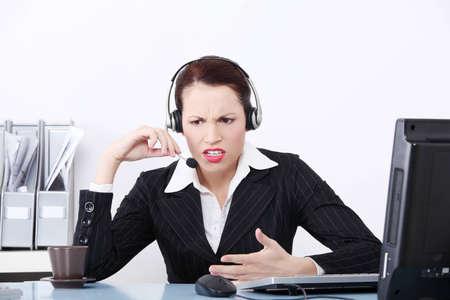 woman issues: Vista frontal de una bella mujer de negocios gritando a trav�s de los auriculares en el trabajo.