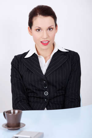 negatively: Front view portrait of a beautiful business woman sitting behind the desk, being negatively surprised.