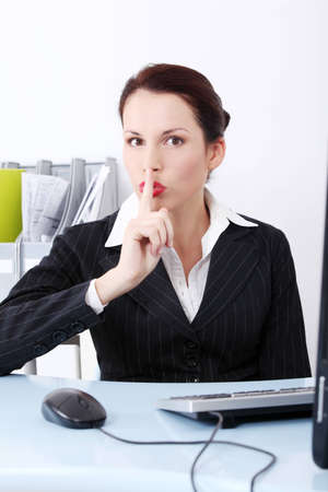stay beautiful: Front view of a beautiful business woman sitting behind the desk, showing to be silent.