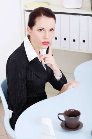 attracive: Site view of a beautiful business woman sitting behind the desk, showing to be silent.