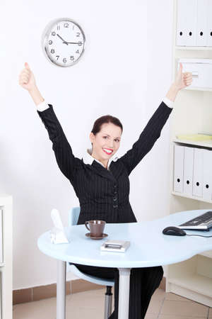 good looking: Pretty caucasian businesswoman with hands in the air gesturing okay sign and sitting behind the desk in the office.