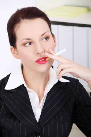 Pretty caucasian businesswoman smoking a cigarette in the office. photo
