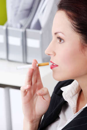 Closeup on pretty caucasian smoking businesswoman in the office.