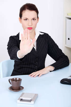 veto: Pretty caucasian businesswoman sitting behind the desk in the office showing stop gesture. Stock Photo