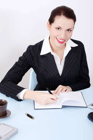 Pretty caucasian businesswoman writing in her notebook in the office. photo