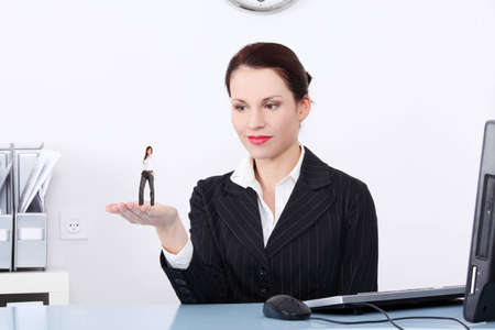 Businesswoman holding a miniature of worker on her hand that she choosed of all applicants. photo
