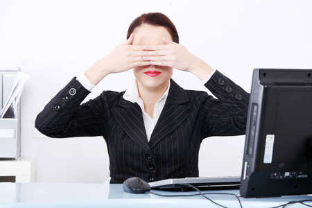 Front view of a beautiful business woman sitting behind the desk in front of the computer, hiding her eyes behind hands, on white. photo