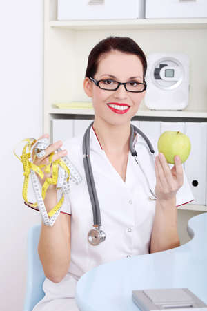 nutritionist: Beautiful caucasian female doctor in white uniform holding apple and measuring tape. Stock Photo
