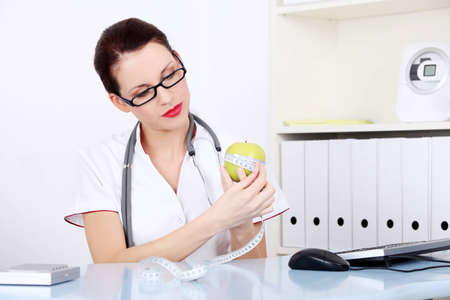nutrition doctor: Caucasian female doctor measuring green apple. Stock Photo
