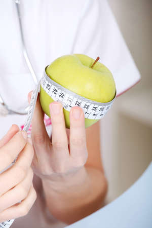 Closeup on measuring apple in caucasian woman`s hands. photo
