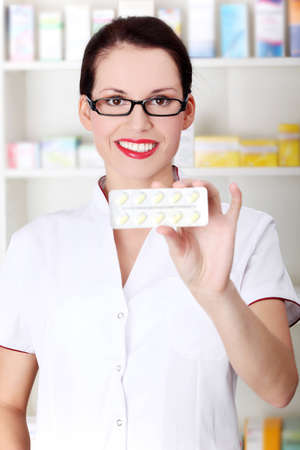 Pretty caucasian pharmacist showing pill blister. photo