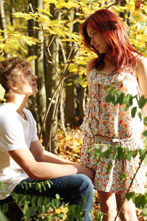 Handsome caucasian boy sitting down with girl standing and looking in his eyes. photo
