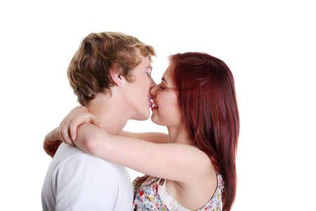Primo piano di giovani coppie caucasiche che si baciano contro la priorità bassa bianca.