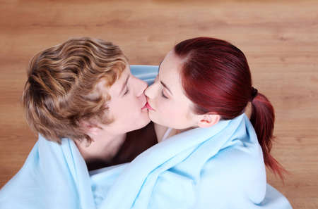 Young caucasian couple kissing wrapped in blue blanket. photo