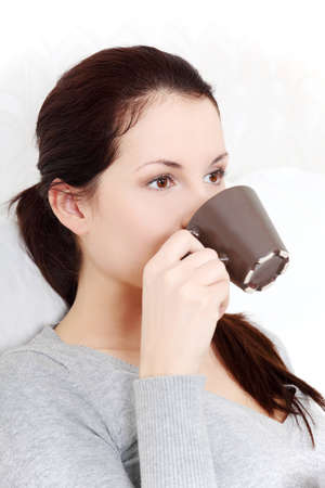 Site view portrait of a young beautiful woman drinking a cup of coffe  tea. photo