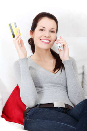 Front view portrait of a young beautiful smiling woman, sitting on a sofa, talking on the phone, rising up the credit card. photo