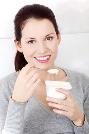 Front view portrait of a beautiful young smiling woman holding a small spoon of yogurt next to her lips. photo