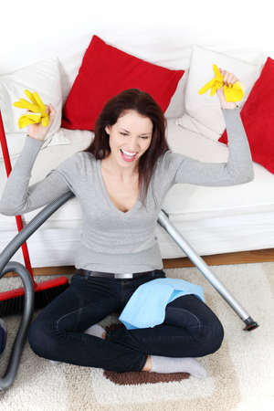 Front view of a full lenght young woman cleaning up at home, sitting on the floor next to the vacuum cleaner and a broom. photo