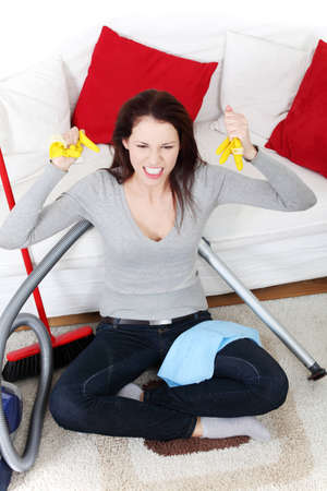 full lenght: Front view of a full lenght young woman cleaning up at home, sitting on the floor next to the vacuum cleaner and a brush, being very angry. Stock Photo
