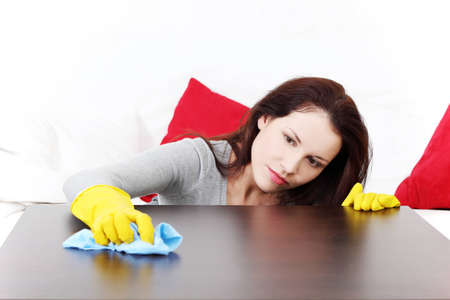 Front view of a young beautiful woman cleaning up the table at home. photo
