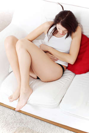 periods: View of a full-lenght beautiful young woman, sitting on a sofa, dressed in underwear and a white t-shirt, having a stomach ache.
