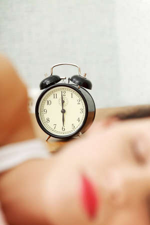 Face closeup of a young beautiful woman sleeping in bed, with a black alarm clock in the background - zoom in on the alarm clock. photo