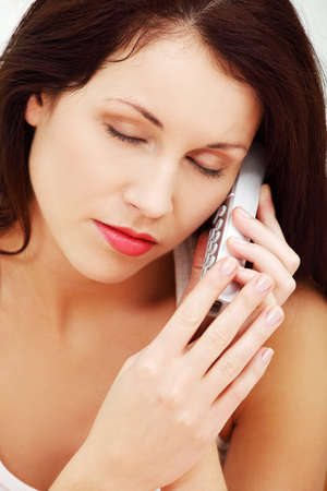 Front view face closeup of a young beautiful woman, being worried during talking on the phone, having her eyes closed up. Stock Photo - 11486744