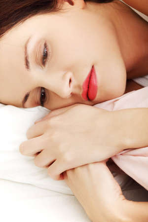 Face closeup of a beautiful young woman lying in bed, cuddling to the sheet and worrying. photo