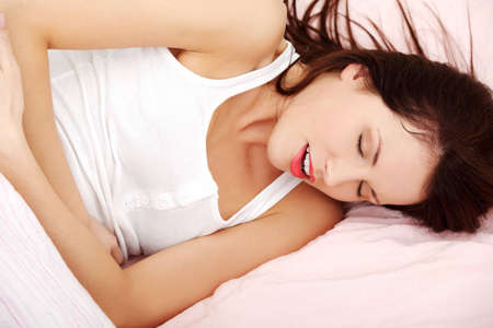 Closeup of a fit and shaped woman having a stomach ache, ambracing her belly in bed. photo