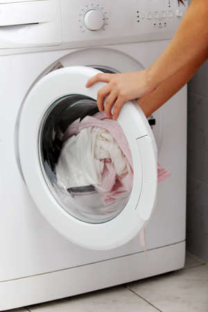 Closeup of a laundry being put into the washing machine. photo