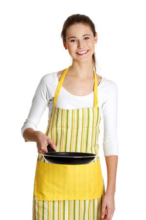 Front view portrait of a young smiling caucasian female teen dressed in apron, holding a frying pan in front of her, on white. Stock Photo - 11486183
